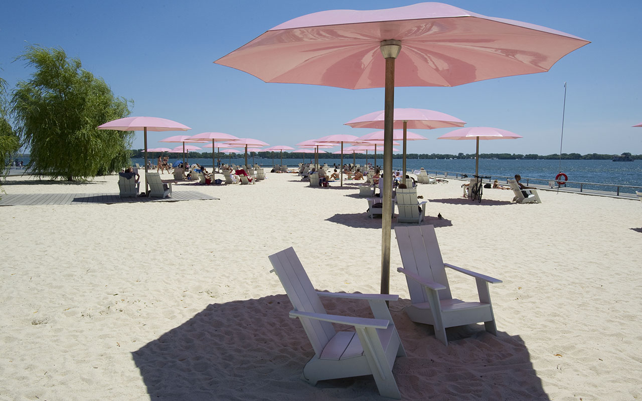 Photo of Sugar Beach, White loungers under pink umbrellas in the white sand of Sugar beach looking out into the harbour