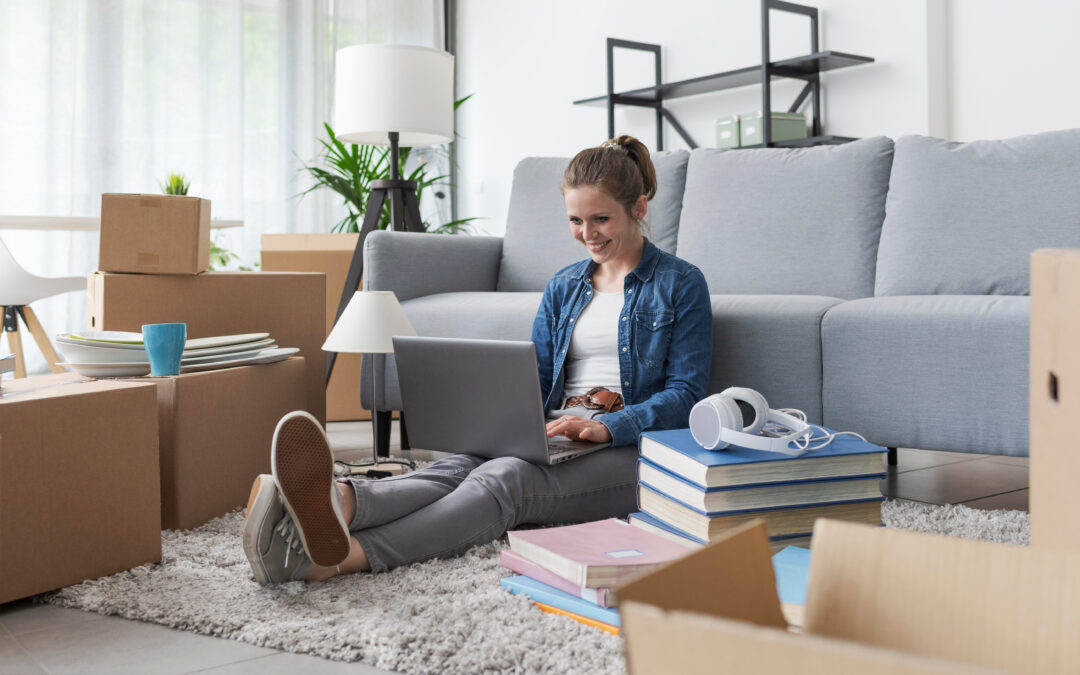 student sitting on the floor of her new apartment with her laptop in her lap and boxes beside her - FAQs about students and auto/property insurance