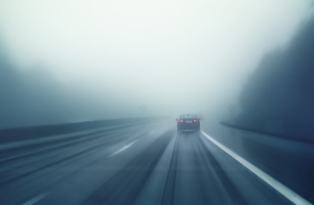 foggy road photo of a car up ahead - driving safely in fog