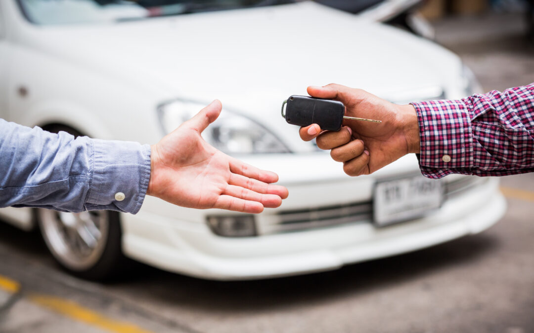 photo of a hand passing keys to another hand in front of a white vehicle - used vehicle information package
