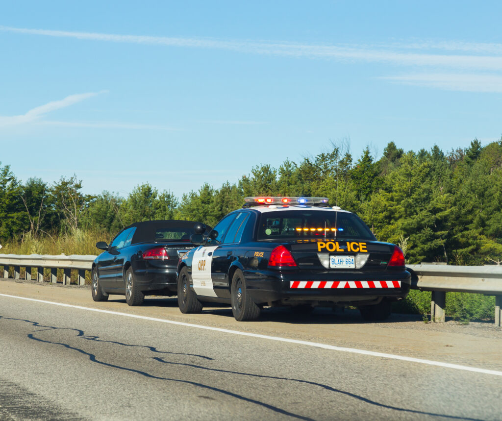 OPP car pulled over to the side of the road with a driver in their vehicle parked in front - driving record of 9